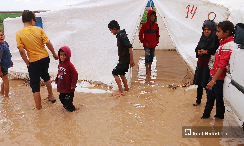 """يمشي الأطفال وسط الماء المتجمع داخل وخارج الخيام في مخيم """"الفلاح"""" بريف حلب الشمالي  - 4 تشرين الثاني 2020 (عنب بلدي/ عبد السلام مجعان)"""