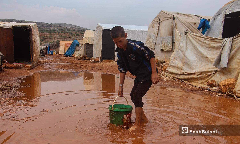 استخدام الدلاء في محاولة إبعاد المياه عن الخيام في مخيم الرمضون على أطراف قرية كفر عروق شمالي إدلب - 2 تشرين الثاني 2020 (عنب بلدي/إياد عبد الجواد)