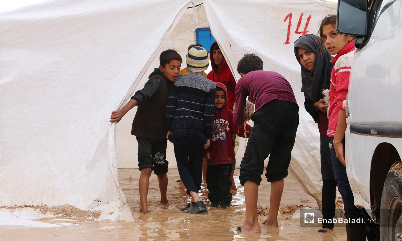 """أطفال متجمعون أمام خيمة غارقة بماء المطر والوحل في مخيم """"الفلاح"""" بريف حلب الشمالي - 4 تشرين الثاني 2020 (عنب بلدي/ عبد السلام مجعان)"""