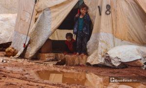 أطفال يقفون على الحجارة التي تحيطها المياه بعد هطول الأمطار الغزيرة على مخيم الرمضون على أطراف قرية كفر عروق شمالي إدلب - 2 تشرين الثاني 2020 (عنب بلدي/إياد عبد الجواد)