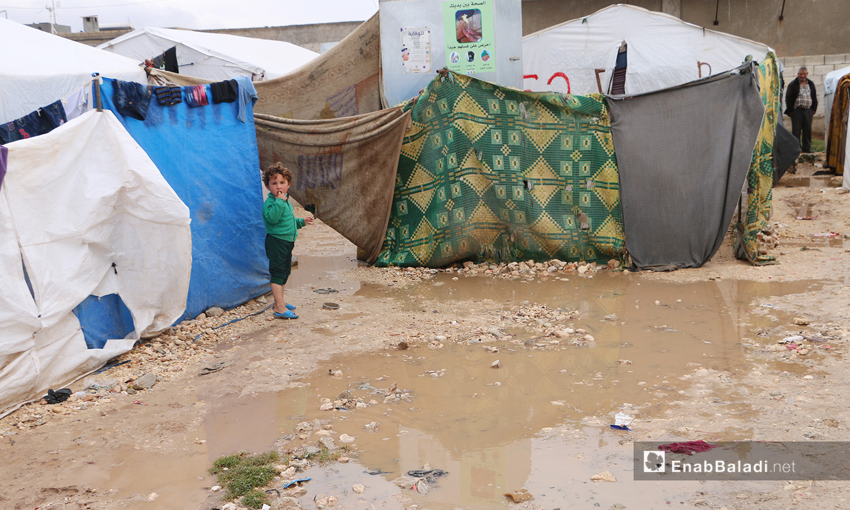 """طفل يقف قرب خيمته التي أحاطت بها ماء الأمطار في مخيم """"الفلاح""""  - 4 تشرين الثاني 2020 (عنب بلدي/ عبد السلام مجعان)"""