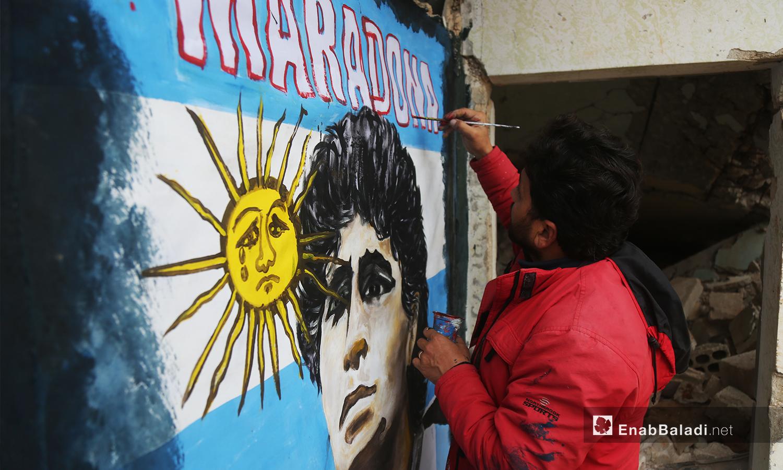 رسام الغرافيتي عزيز أسمر يرسم نجم كرة القدم الأرجنتيني الراحل دييغو مارادونا - 26 تشرين الثاني 2020 (عنب بلدي/ يوسف غريبي)