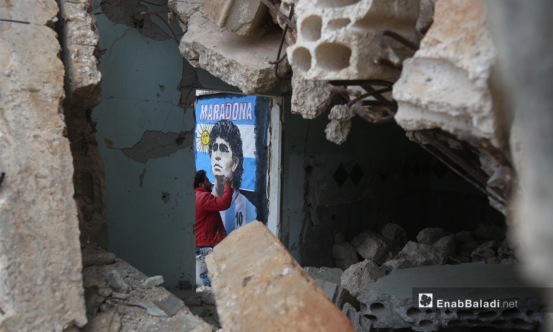 من بين الحجارة المهدمة في منزل مهجور في مدينة بنش يظهر الرسام عزيز أسمر وهو يضع لمساته الأخيرة على جدارية تمثل لاعب كرة القدم الأرجنتيني دييغو مارادونا - 26 تشرين الثاني 2020 (عنب بلدي/ يوسف غريبي)