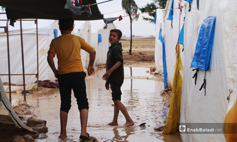 """طفلان يضحكان وهما يمشيان وسط الماء المتجمع بين الخيام في مخيم """"الفلاح"""" بريف حلب الشمالي  - 4 تشرين الثاني 2020 (عنب بلدي/ عبد السلام مجعان)"""