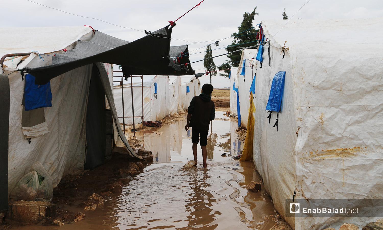 """طفل يخوض في الماء الذي أغرق مخيم """"الفلاح"""" بريف حلب الشمالي والذي يخلو من التجهيزات الملائمة للأمطار الشتوية  - 4 تشرين الثاني 2020 (عنب بلدي/ عبد السلام مجعان)"""