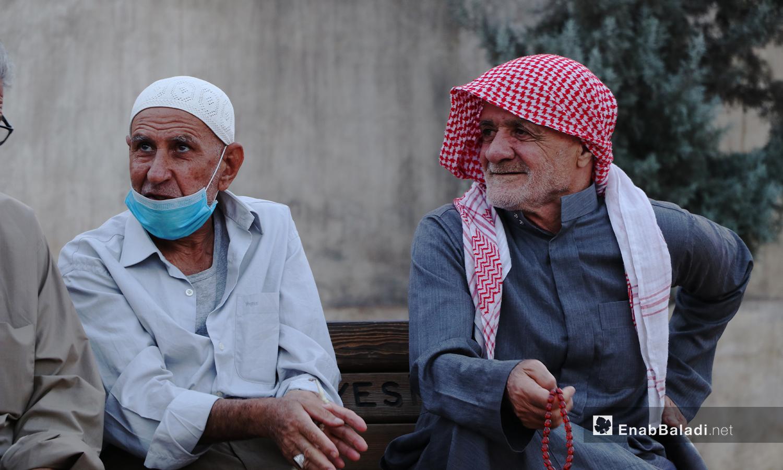 رجلان كبيران في السن في مدينة الباب بريف حلب الشمالي يجلسان على مقربة من بعضهما البعض في حين ينزل أحدهما الكمامة التي يرتديها إلى ذقنه - 24 تشرين الثاني 2020 (عنب بلدي/ عاصم الملحم)