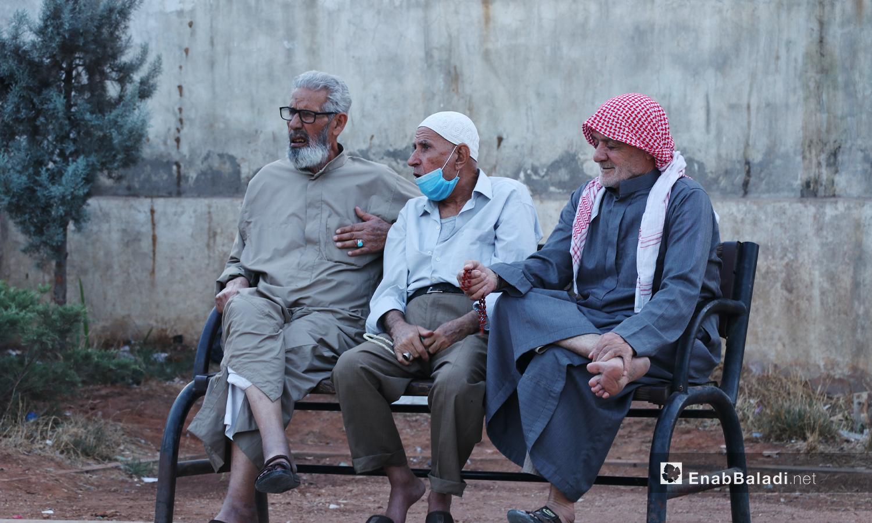ثلاثة رجال يجلسون على مقعد في أحد شوارع مدينة الباب بريف حلب الشمالي دون الالتزام بالتباعد الاجتماعي في حين ينزل أحدهم الكمامة التي يرتديها إلى ذقنه - 24 تشرين الثاني 2020 (عنب بلدي/ عاصم الملحم)