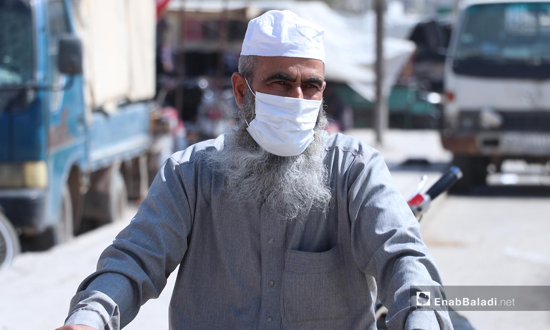 """يرتدي رجل كبير في السن الكمامة وهو يركب على الدراجة النارية في أحد شوارع مدينة الباب بريف حلب الشمالي ازدحام في سوق مدينة الباب رغم وصفها بالـ""""منكوبة"""" بسبب ارتفاع أعداد الإصابات بفيروس """"كورونا"""" -24 تشرين الثاني 2020 (عنب بلدي/ عاصم الملحم)"""