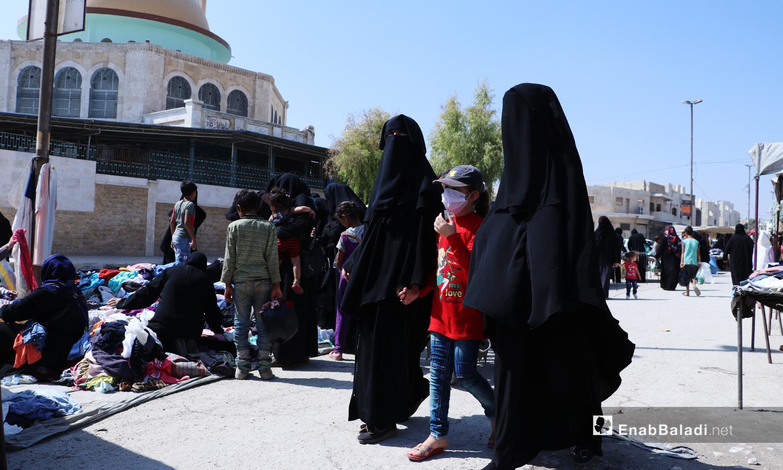 ترتدي فتاة صغيرة الكمامة وهي تمشي مع امرأتين ترتديان النقاب في البازار الشعبي في مدينة الباب بريف حلب الشمالي - 24 تشرين الثاني 2020 (عنب بلدي/ عاصم الملحم)