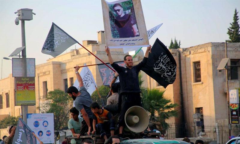 متظاهرون يرفعون الأعلام الإسلامية وصورة لعبد الله أنزوروف الشاب الشيشاني الذي قطع رأس مدرس للغة الفرنسية بالقرب من باريس - 28 تشرين الأول 2020 (AFP)