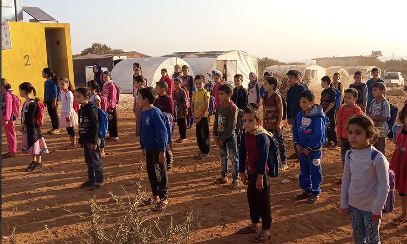طلاب مدرسة مخيم أبيض قرب مدينة معرة مصرين يتابعون تعليمهم رغم الحاجة للكثير من مقوماته (مديرية التربية في إدلب)