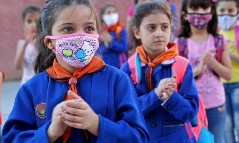 طلاب في مدرسة بدمشق قبل دخول فصولهم الدراسية مع انطلاق العام الدراسي (رويترز)
