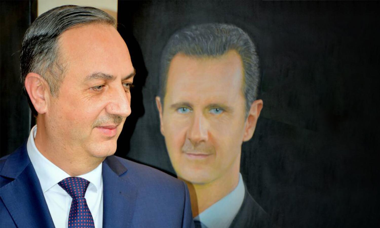 محافظ ريف دمشق علاء منير إبراهيم وخلفه صورة لرئيس النظام السوري بشار الأسد (صفحة الفنانون التشكيليون/ فيس بوك)