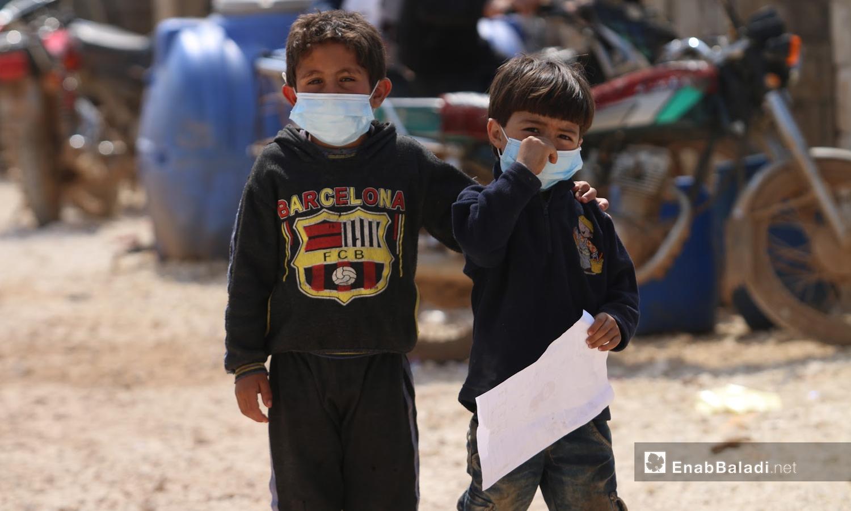 """طفلان يرتديان الكمامة للحماية من فيروس """"كورونا"""" في مخيمات أطمة بريف إدلب الشمالي - 17 آذار 2020 (عنب بلدي/ يوسف غريبي)"""