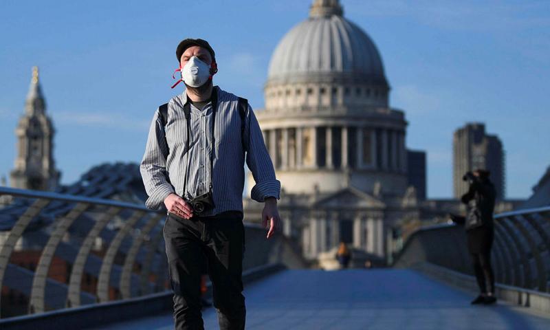 """مواطن في بريطانيا يتخذ الإجراءات الاحترازية خلال الحظر لمواجهة فيروس """"كورونا"""" (EPA)"""