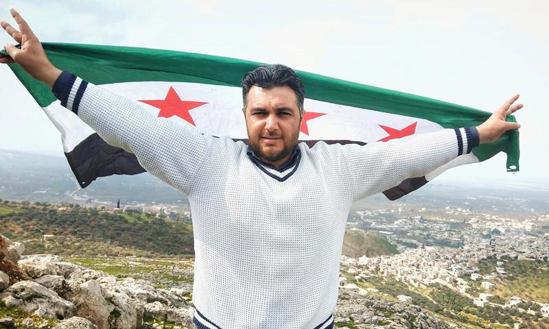الناشط الإعلامي حسين خطاب يرفع علم الثورة السورية (صفحة خطاب في فيس بوك)