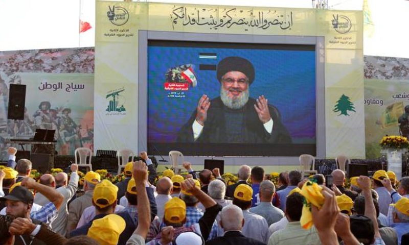 الأمين العام لحزب الله اللبناني حسن نصر الله يلق خطاب عبر الشاشة أمام حشد من أتباعه (رويترز)