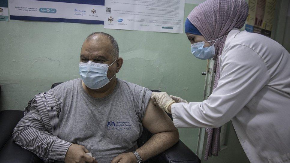 """عامل طبي يعطي جرعة من لقاح فيروس """"كورونا"""" في عيادة التطعيمات في إربد في الأردن المفوضية السامية لشؤون اللاجئين_14 من كانون الثاني 2021"""