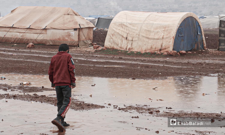 """طفل يقف أمام مخيمات منطقة """"أرض الوطى""""  الغارقة بمياه العاصفة المطرية - 14 كانون الثاني 2021 (عنب بلدي / إياد عبد الجواد)"""
