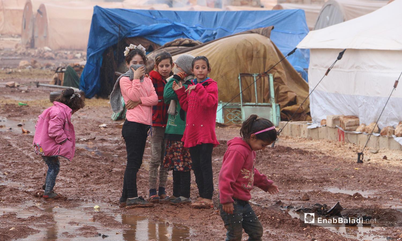 """أطفال المخيم يلعبون بالوحل بعد إنتهاء العاصفة المطرية في مخيمات منطقة """"الوطى"""" - 14 كانون الثاني 2021 (عنب بلدي / إياد عبد الجواد)"""