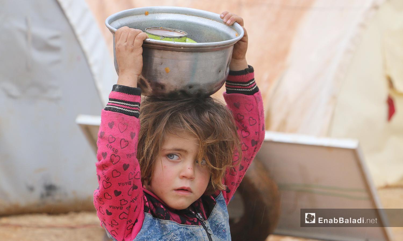 """طفلة تنقل المياه إلى خيمتها في مخيمات """"الوطى""""في مدينة إدلب - 14 كانون الثاني 2021 (عنب بلدي / إياد عبد الجواد)"""