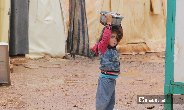 """طفلة تنقل المياه إلى خيمتها في مخيمات """"الوطى""""في إدلب - 14 كانون الثاني 2021 (عنب بلدي / إياد عبد الجواد)"""