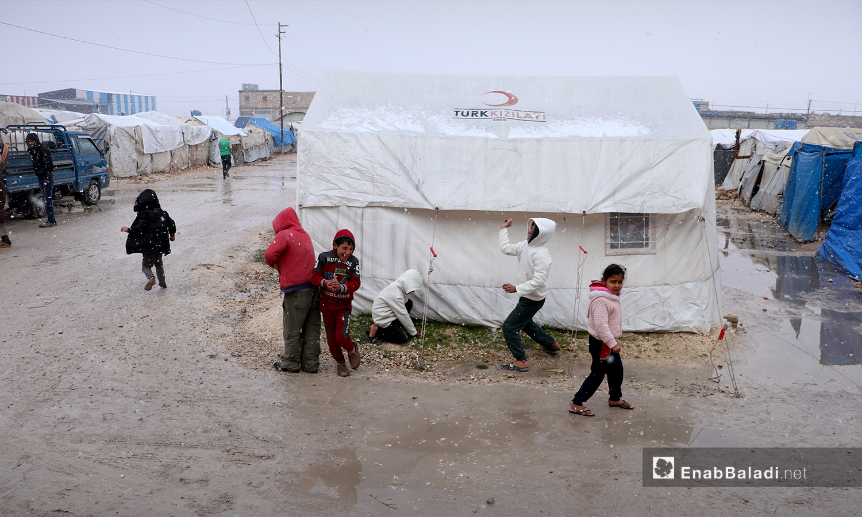 أطفال يلعبون بالثلوج في مخيم ضيوف الشرقية بمدينة الباب بريف حلب الشمالي - 20 كانون الثاني 2021 (عنب بلدي - عاصم الملحم)