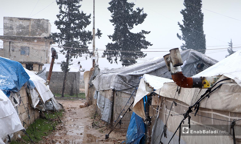 تساقط الثلوج فوق الخيام في مخيم ضيوف الشرقية أثناء تساقط الثلوج بمدينة الباب بريف حلب الشمالي - 20 كانون الثاني 2021 (عنب بلدي - عاصم الملحم)