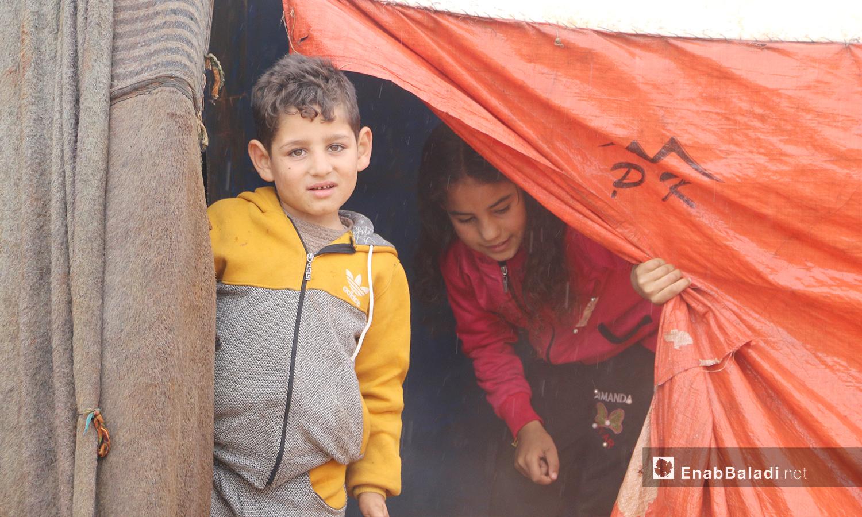 """أطفال يخرجون من خيمتهم بعد إنتهاء العاصفة المطرية في مخيمات منطقة """"الوطى"""" في إدلب - 14 كانون الثاني 2021 (عنب بلدي / إياد عبد الجواد)"""