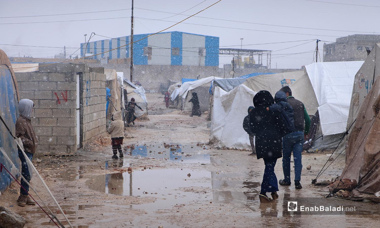 أطفال في مخيم ضيوف الشرقية أثناء تساقط الثلوج بمدينة الباب بريف حلب الشمالي - 20 كانون الثاني 2021 (عنب بلدي - عاصم الملحم)
