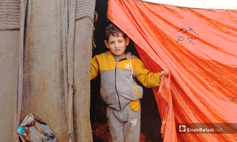 """طفل خرج من خيمته بعد إنتهاء العاصفة المطرية في مخيمات منطقة """"الوطى"""" في إدلب - 14 كانون الثاني 2021 (عنب بلدي / إياد عبد الجواد)"""