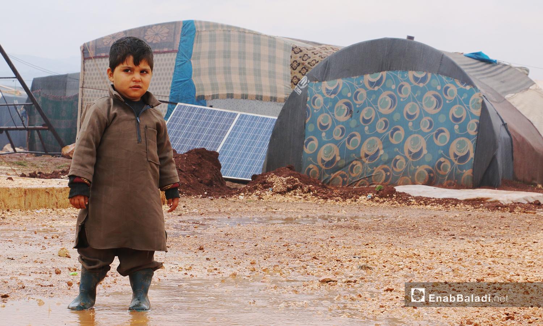 """طفل تغمر قدماه مياه العاصفة المطرية في مخيمات منطقة """" الوطى""""- 14 كانون الثاني 2021 (عنب بلدي / إياد عبد الجواد)"""