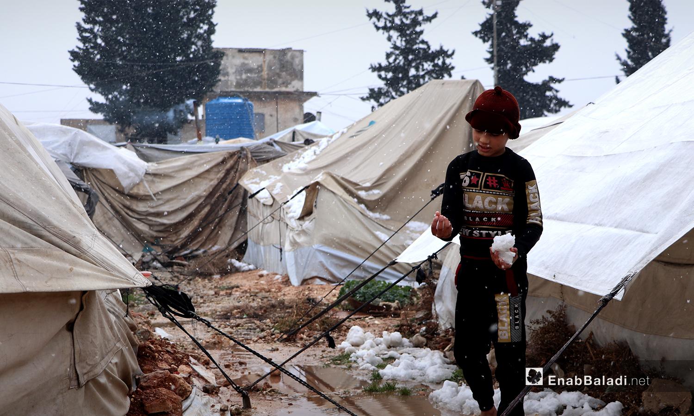 طفل يلعب بالثلوج في مخيم ضيوف الشرقية بمدينة الباب بريف حلب الشمالي - 20 كانون الثاني 2021 (عنب بلدي - عاصم الملحم)