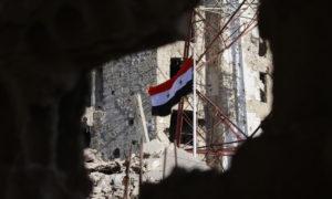 علم النظام في المناطق المدمرة من درعا - تموز 2018 (AFP)