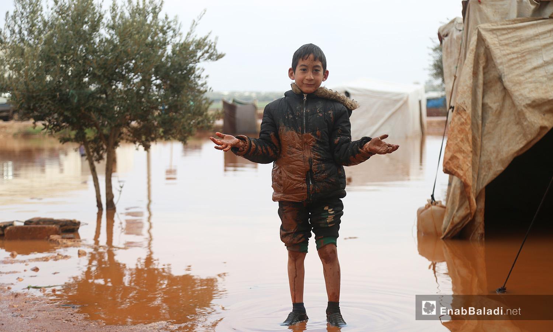 طفل يقف وسط الخيام الغارقة بمياه الأمطار في مخيم حربنوش بريف إدلب - 19 كانون الثاني 2021 (عنب بلدي - يوسف غريبي)