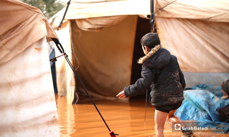 طفل يمشي بين الخيام الغارقة بمياه الأمطار في مخيم حربنوش بريف إدلب - 19 كانون الثاني 2021 (عنب بلدي - يوسف غريبي)