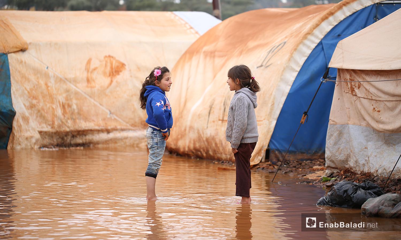 طفلتان تقفان بين الخيام الغارقة بمياه الأمطار في مخيم حربنوش بريف إدلب - 19 كانون الثاني 2021 (عنب بلدي - يوسف غريبي)