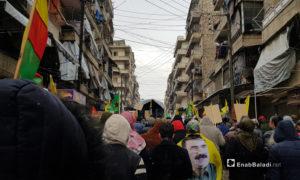 """مسيرة في حي الشيخ مقصود بحلب تندد بذكرى انطلاق عملية """"غصن الزيتون"""" التي انتهت بالسيطرة التركية على عفرين عام 2018 يرفع المشاركون أعلام """"الإدارة الذاتية"""" التي تسيطر على الحي وصور عبد الله أوجلان مؤسس """"حزب العمال الكردستاني"""" - 20 كانون الثاني 2021 (عنب بلدي)"""