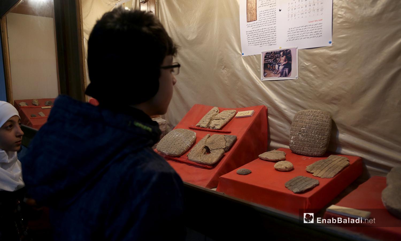 طفل ينظر إلى القطع الأثرية في متحف مدينة إدلب - 18 شباط 2021 (عنب بلدي/يوسف غريبي)