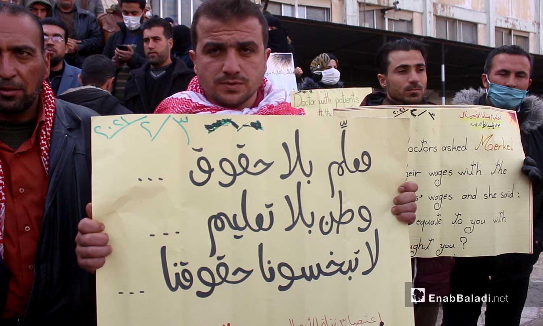 معلم في مدينة إدلب يرفع لافتة ضمن اعتصام بناة الأجيال أمام مديرية التربية بسبب انقطاع الرواتب منذ عامين - 3 شباط 2021 (عنب بلدي - أنس الخولي)