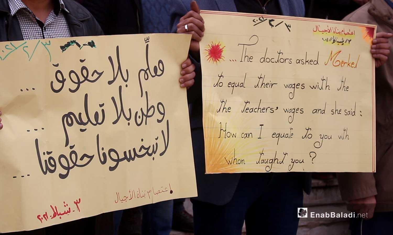لافتات احتجاجية يرفعها معلمون أمام مديرية التربية في مدينة إدلب ضمن اعتصام بناة الأجيال  - 3 شباط 2021 (عنب بلدي - أنس الخولي)