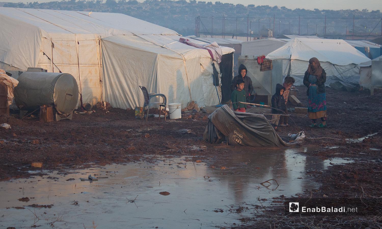 أطفال يقفون أمام خيمتهم أثناء تشكل الصقيع  بريف إدلب - 23 كانون الثاني 2021 (عنب بلدي - إياد أبو الجود)