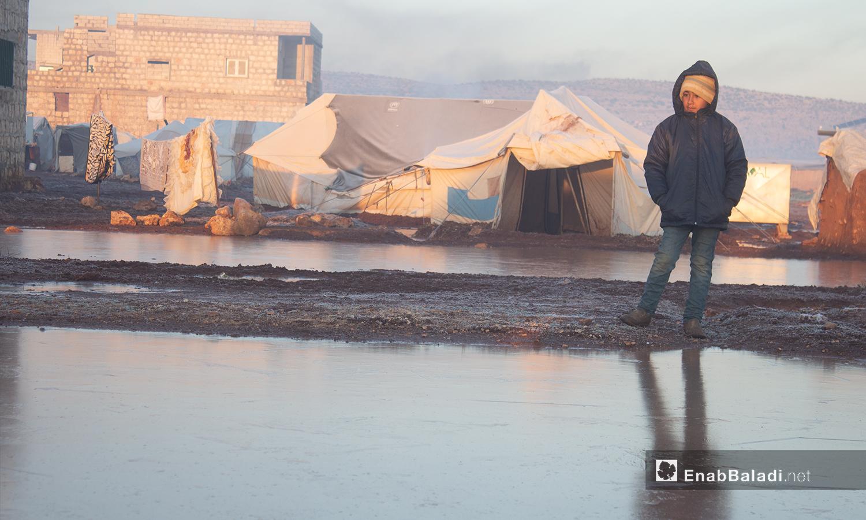 طفل يقف في مخيم كفرعروق بريف إدلب أثناء تشكل الصقيع - 23 كانون الثاني 2021 (عنب بلدي - إياد أبو الجود)