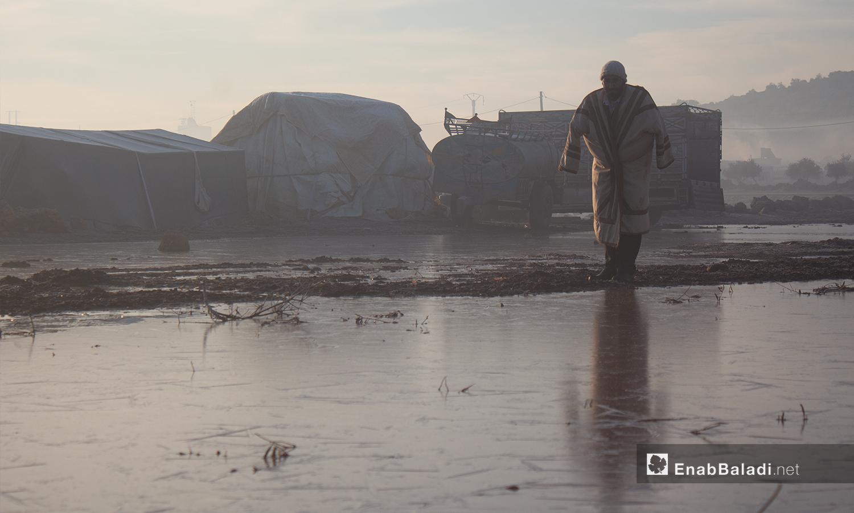 رجل يمشي في مخيم كفرعروق بريف إدلب أثناء تشكل الصقيع - 23 كانون الثاني 2021 (عنب بلدي - إياد أبو الجود)