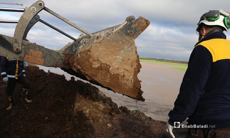 الدفاع المدني يرفع سواتر ترابية في بلدة دابق على جانب نهر قويق لمنع وصول مياه النهر إلى البلدة والمخيمات القريبة - 31 كانون الثاني 2021 (عنب بلدي - عبد السلام مجعان)