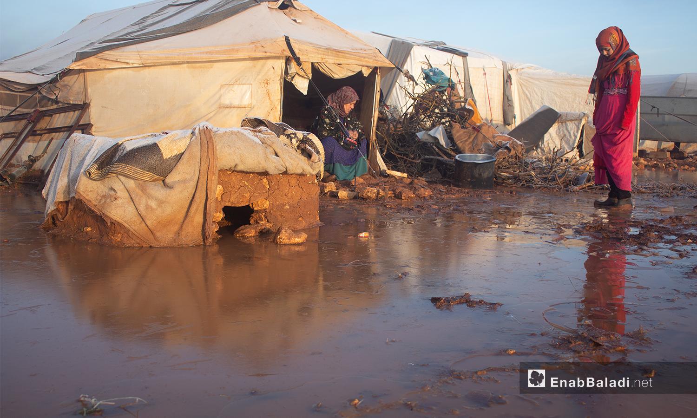 إمرأة تجلس بخيمتها بمخيم كفرعروق أثناء الصقيع بريف إدلب - 23 كانون الثاني 2021 (عنب بلدي - إياد أبو الجود)