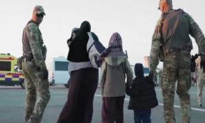 """عسكريون كازاخستانيون يرافقون عائلة كازاخستانية أثناء إعادتهم من سوريا خلال عملية """"زوسان"""" (Courtesy Photo)"""