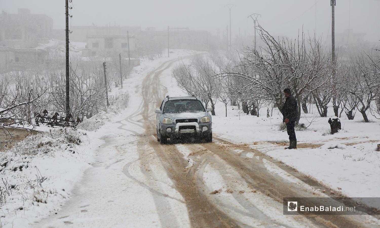 سيارة ورجل على طريق أرنبة معراته أثناء الثلوج على جبل الزاوية جنوب إدلب - 17 شباط 2021 (عنب بلدي/ يوسف غريبي)