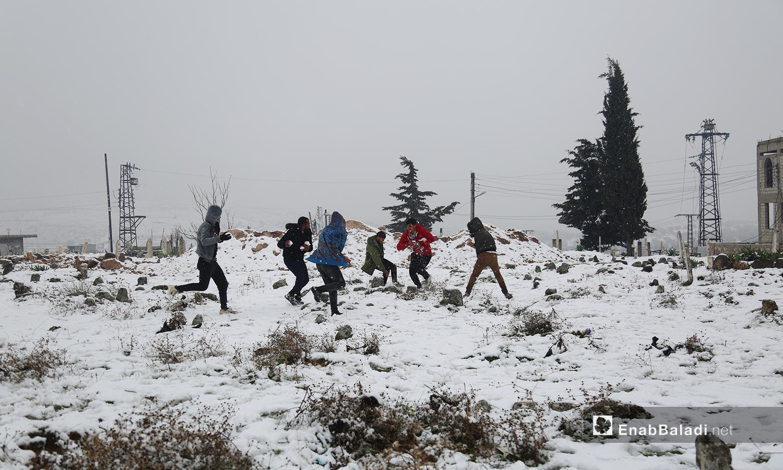 أطفال يلعبون في الثلج في بلدة معرات في جبل الزاوية جنوب إدلب  - 17 شباط 2021 (عنب بلدي/ يوسف غريبي)