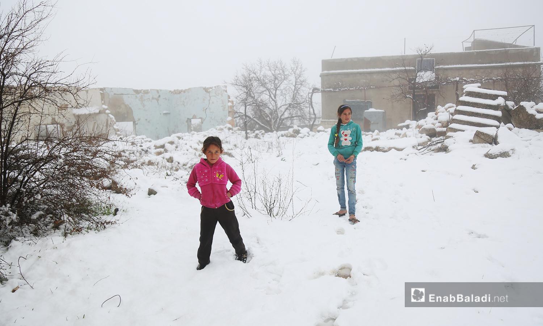 أطفال يقفون على الثلج في بلدة عين لاروز بجبل الزاوية جنوب إدلب -17 شباط 2021 (عنب بلدي/ يوسف غريبي)